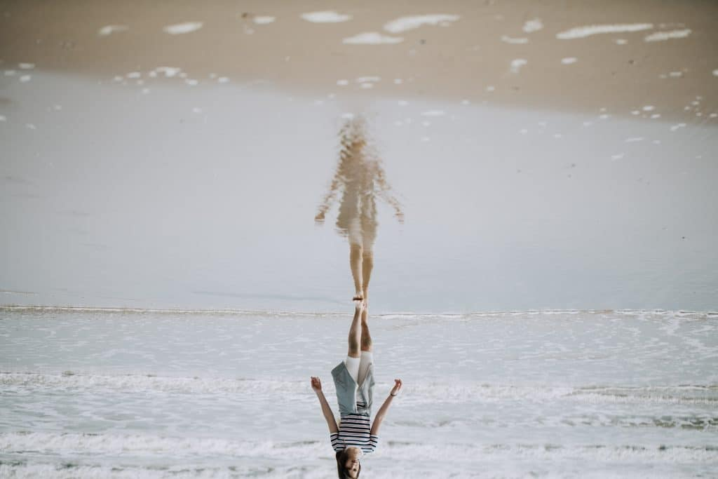 Mulher caminhando à beira da praia, com sua imagem refletida na água do mar.
