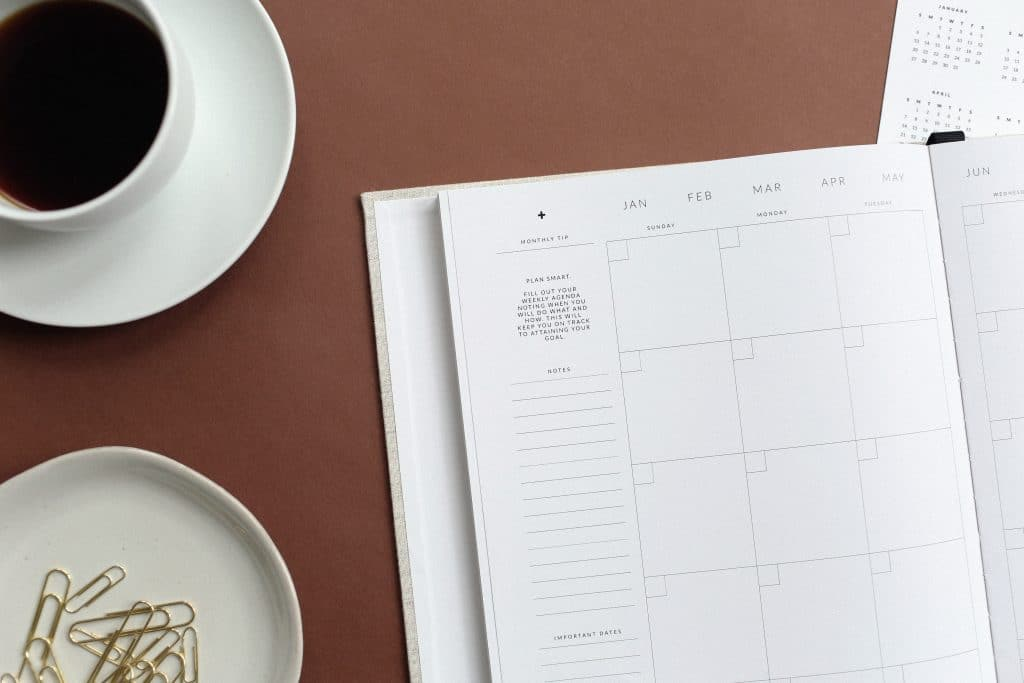 Agenda disposta sobre uma mesa, ao lado de grampos de papel e uma xícara de café.