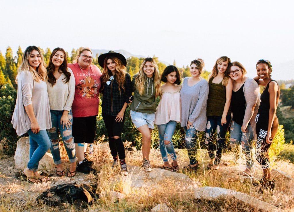 Grupo de mulheres com etnias, pesos e alturas diferentes, se abraçando lado a lado, em campo aberto.