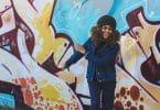 Mulher sorrindo com os olhos fechados de frente para um muro colorido