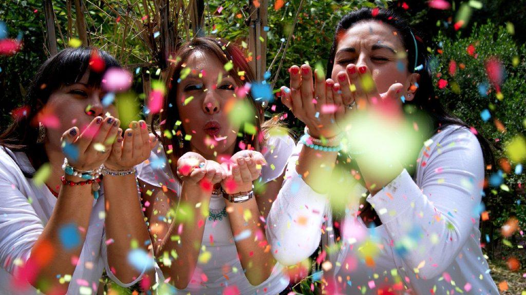 Três mulheres vestindo camisa na cor brnaca. Elas estão felizes e assoprando papeis picados coloridos.