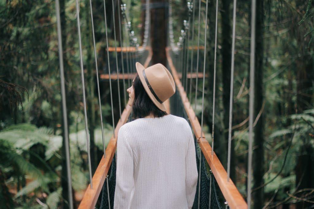 Imagem de uma mulher atravessando um ponte no meio de uma floresta. Ela está usando roupas claras e um chapéu clássico na cor bege.