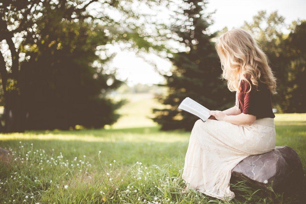 Imagem de um lindo campo verde. Nele encontra-se uma linda mulher loura de cabelos longos. Ela está sentada sobre uma pedra e fazendo a leitura de um livro.