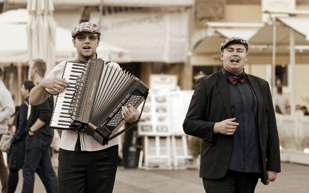 Dois homens jovens usando boina e roupa social. Eles estão em uma praça aberta. Ambos estão cantando e um deles tocando sanfona.