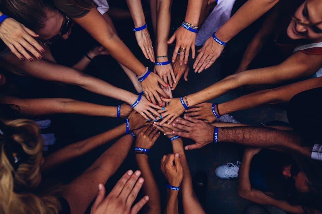 Grupo de pessoas em círculo com as mãos unidas ao meio.