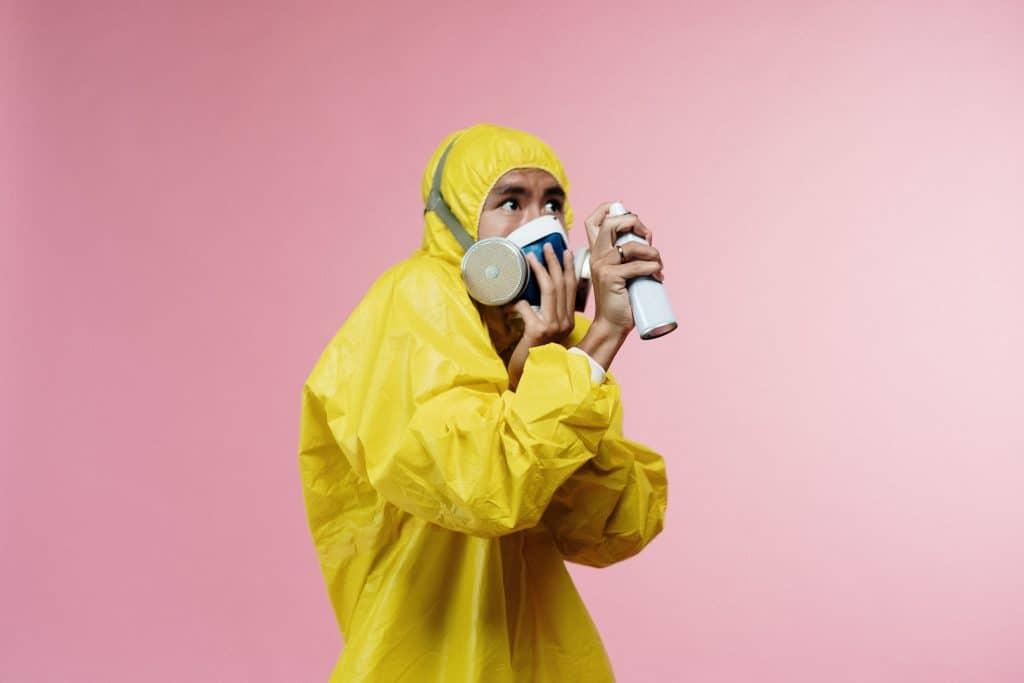 Pessoa usando máscara e capa plástica enquanto espirra um desinfetante pelo ar.