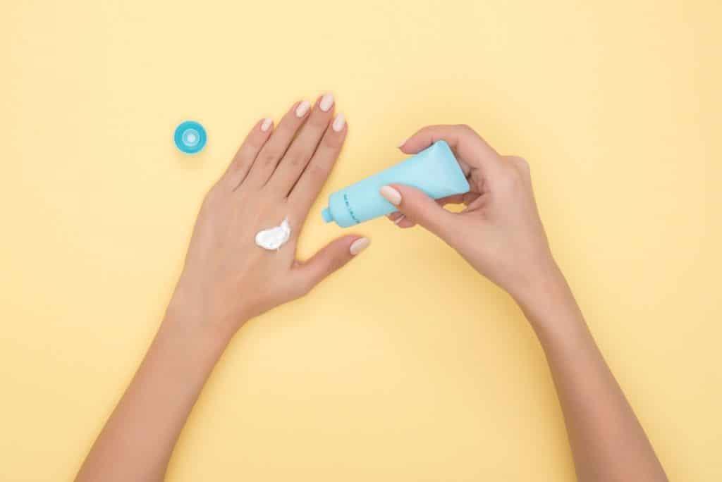 Mãos de uma pessoa passando protetor solar em si mesma.