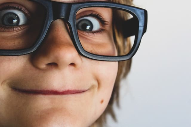 Rosto de criança visto de perto com óculos sem lente e olhos azuis