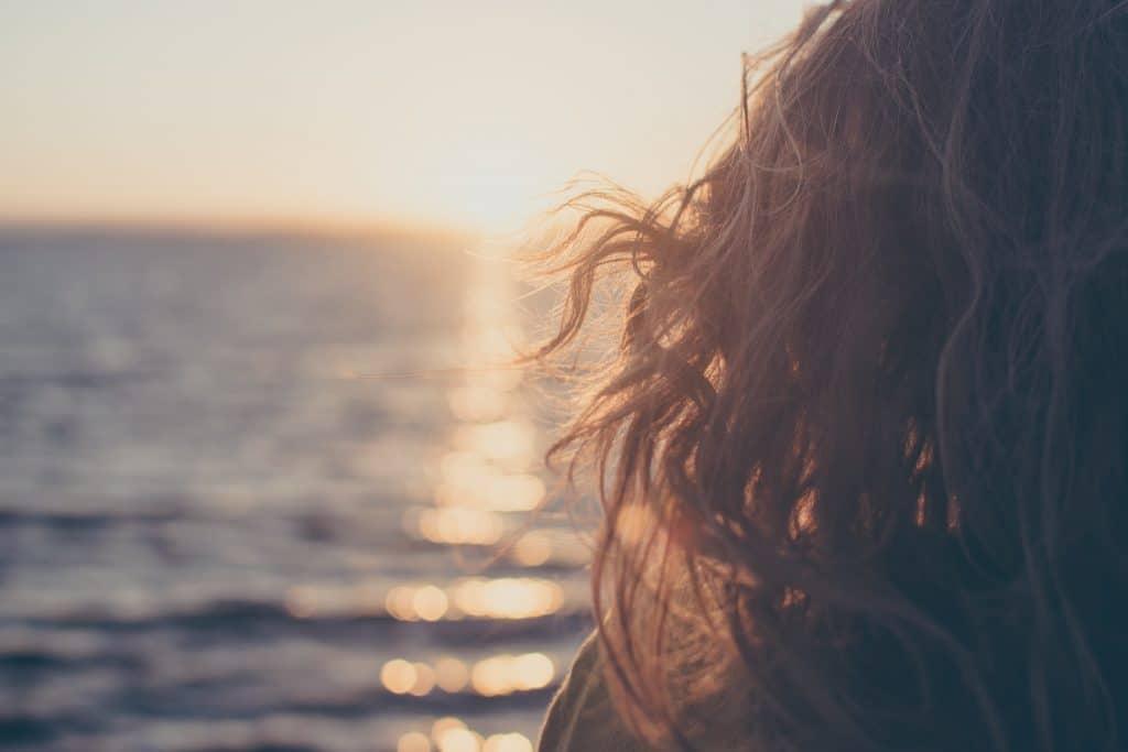 Mulher olhando para o mar e o pôr do sol