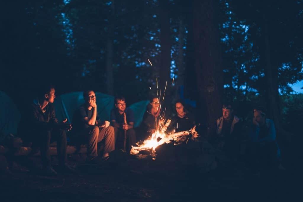 Pessoas reunidas em volta a fogueira em uma floresta, contando histórias.