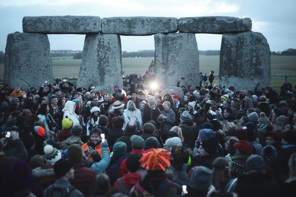 Muitas pessoas reunidas no monumento Stonehenge, na Inglaterra, durante o amanhecer no Solstício de Inverno.