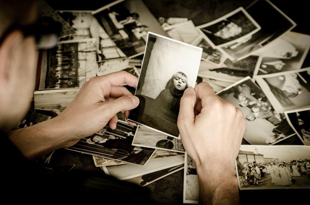 Imagem de uma mesa e sobre ela várias fotos em preto e branco. Um homem está mexendo nessas fotos e ele segura entre as mãos a foto de uma criança.