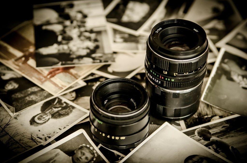 Imagem de várias fotos em preto e branco espalhadas sobre uma mesa. Sobre as fotos temos duas lentes de câmara fotográfica.