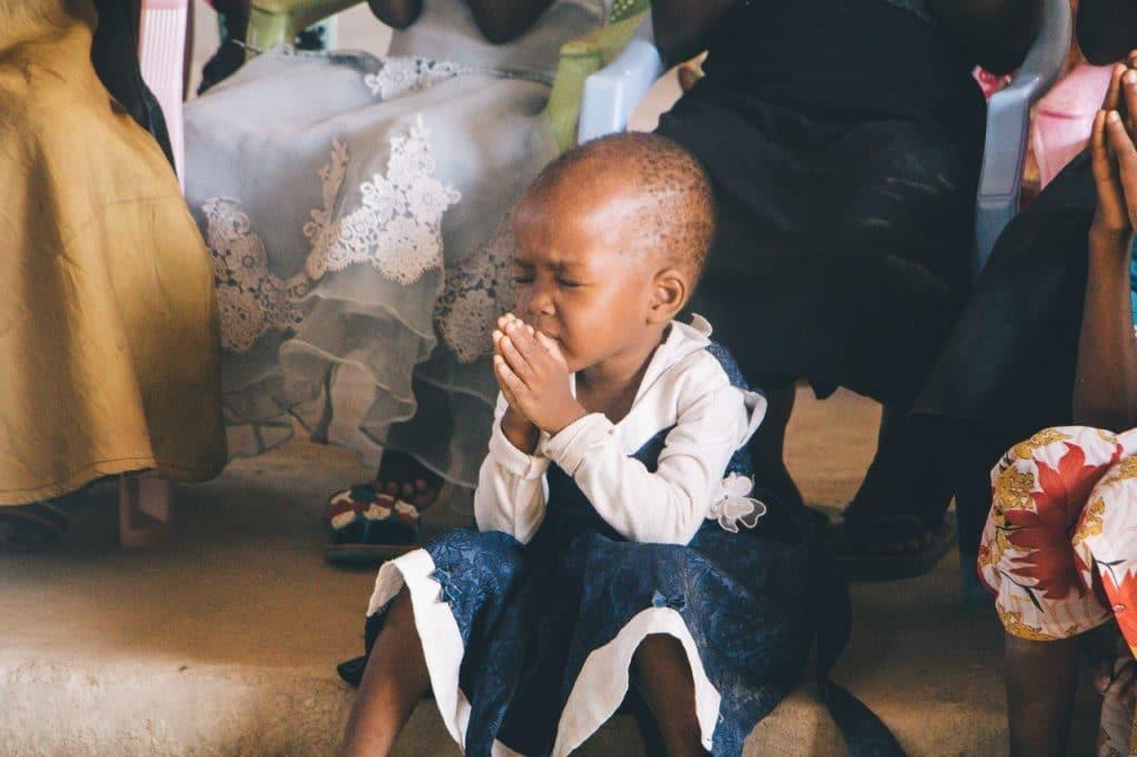 Foto de uma criança sentada no chão, de olhos fechados, rezando.