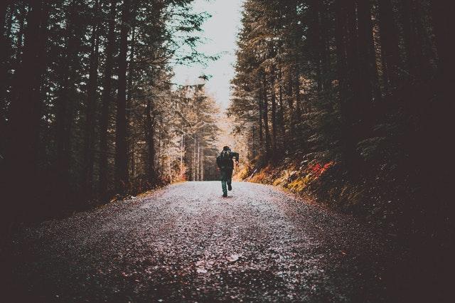 Homem de costas correndo em subida de estrada de pedras em floresta