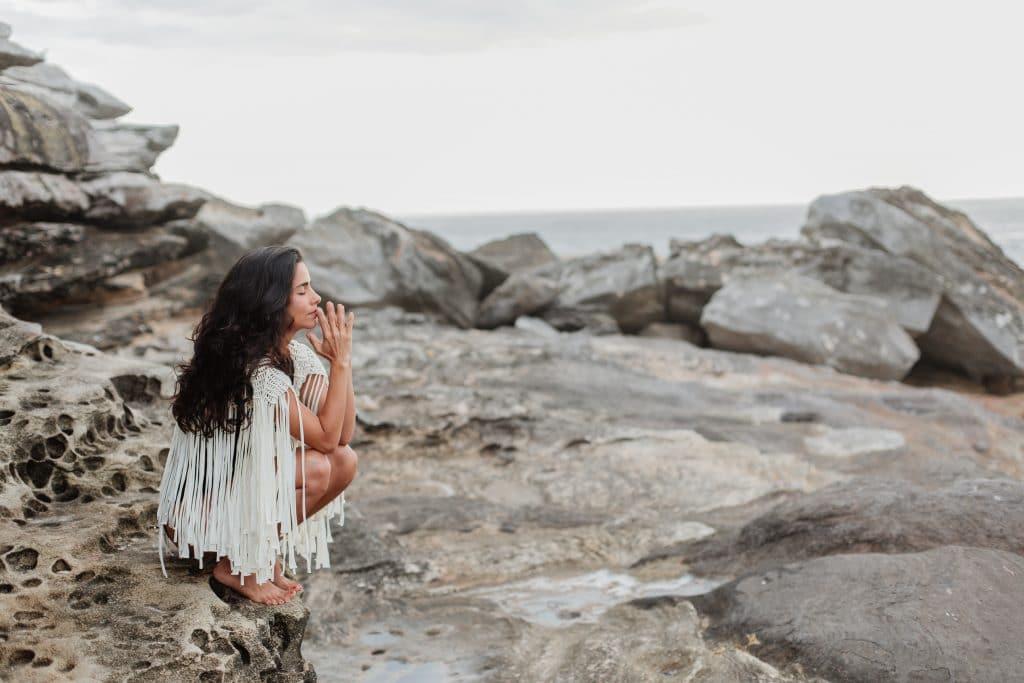 Mulher agachada com olhos fechados em pedras com mar ao fundo