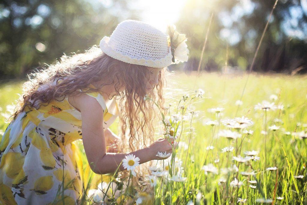 Criança vestindo um lindo vestido amarelho e usando um chapeu de crochê branco. Ela está em um campo de flores colhendo margaridas.