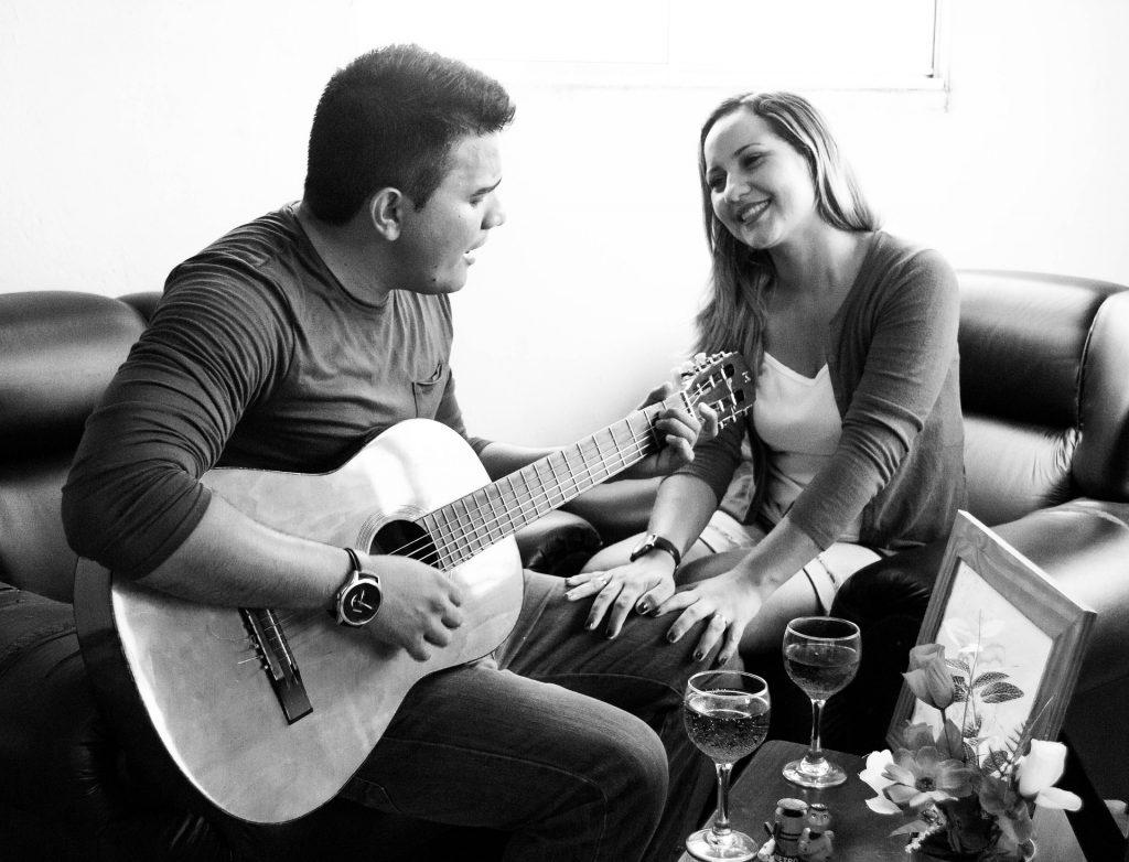 Imagem de um casal de homem e mulher. Eles estão em um sala, sentados cada um do lado do outro. Ele canta para ela e toca uma música em seu violão.