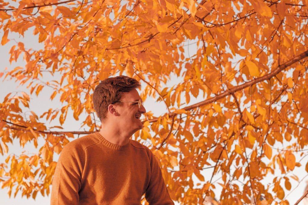 Homem visto de perfil, usando um suéter e óculos, sorrindo na frente de uma árvore de outono, com folhas secas.
