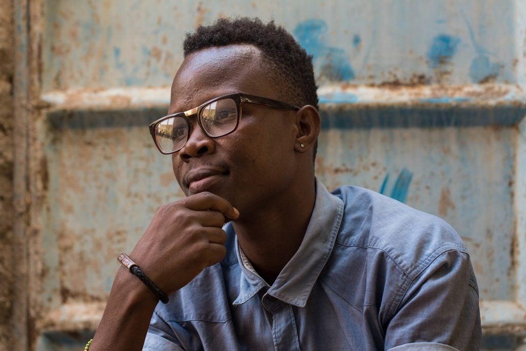 Imagem de um jovem negro pensativo. Ele está com uma das mãos segurando o queixo e veste uma camisa jeans azul clara e usa um óculos de grau.