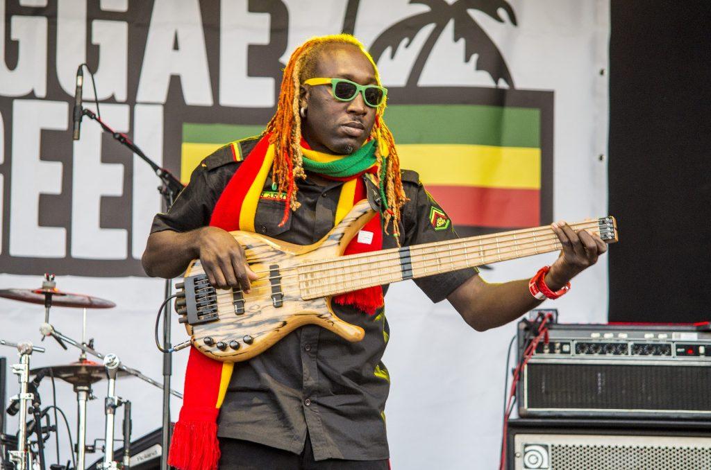 Músico de reggae fazendo uma apresentação em um show do estilo musical. Ele faz uma apresentação solo, tocando uma guitarra. Usa cachecol com as cores do reggae, um rastafari e um óculos de sol nas cores verde e amarelo.