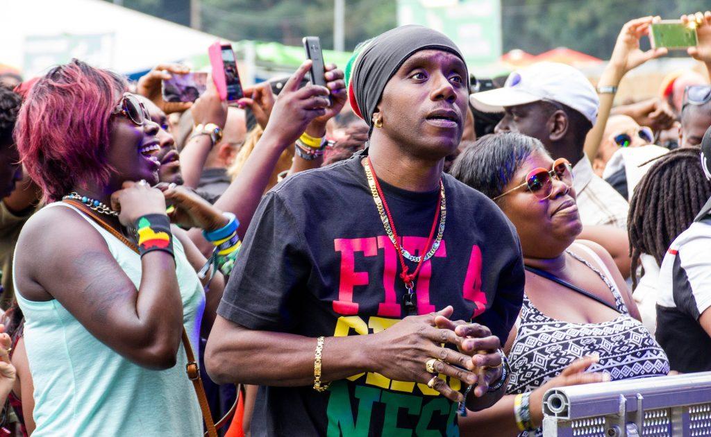 Grande massa de público que curte o estilo reggae participando de um show em uma praça pública.