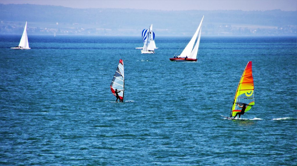 Homens participando de uma competição de veleiro em um lindo lago azul.