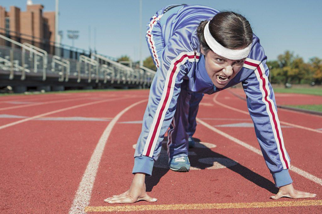 Mulher vestida com um agasalho cinza claro com listras brancas e vermelha e com uma faixa branca na cabeça. Ela está em uma pista de corrida em posição de largada.