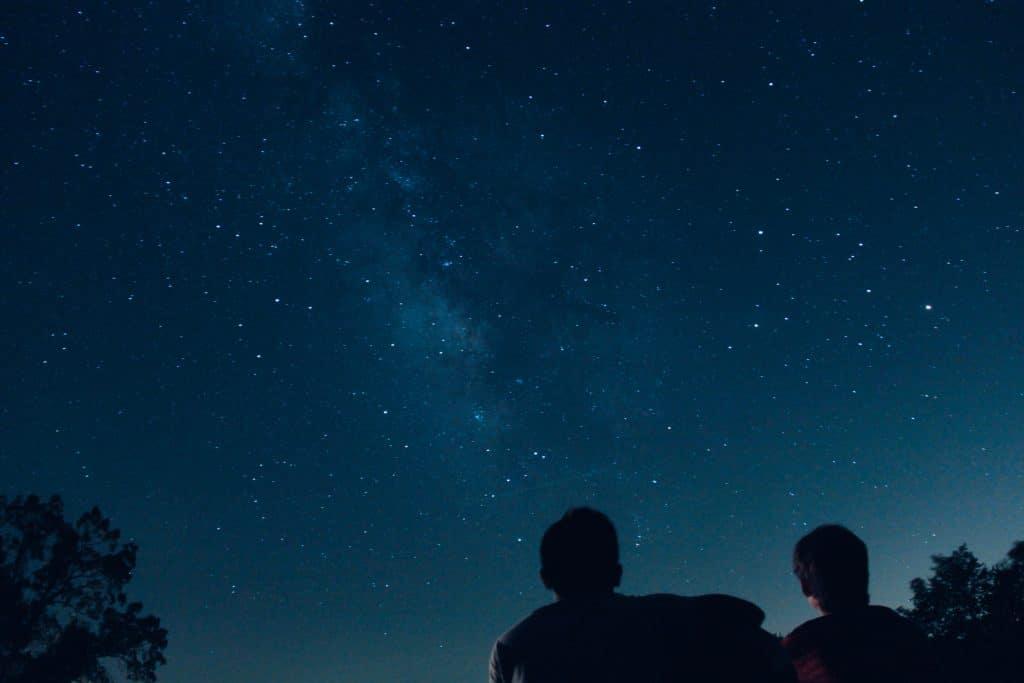 Silhueta de duas pessoas admirando as estrelas.