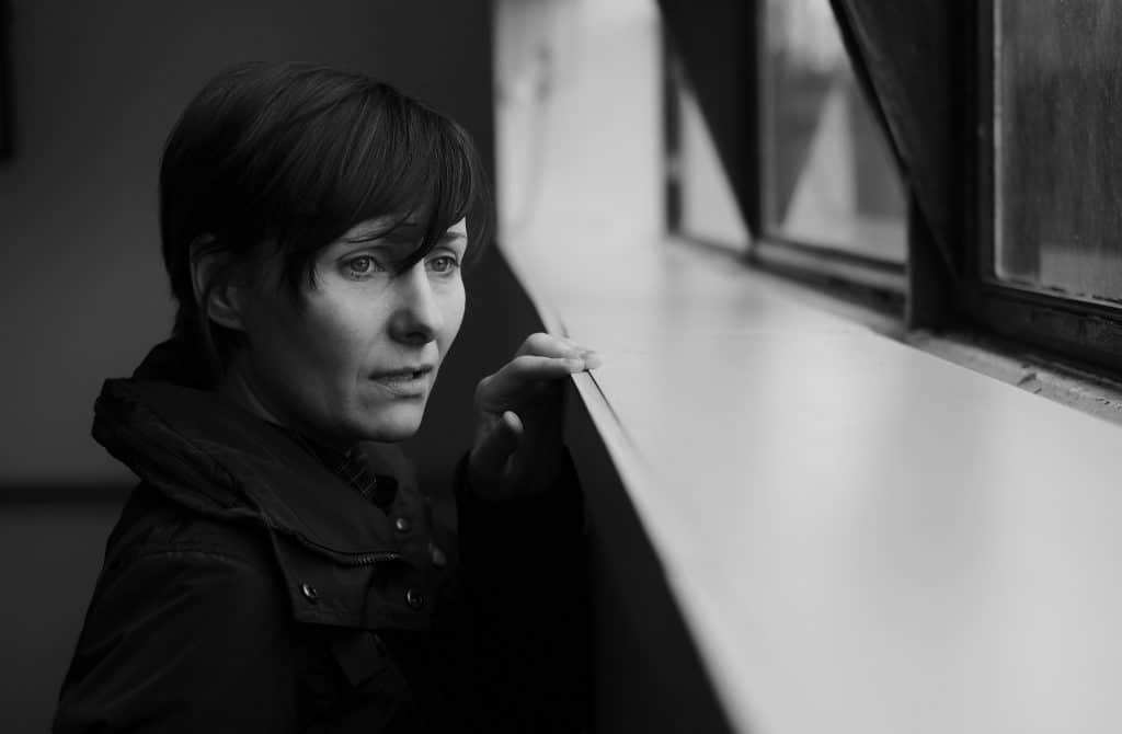 Mulher olhando pela janela com o semblante triste. - Imagem de luto