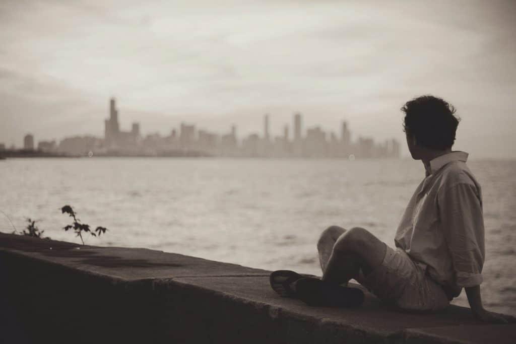 Imagem de um homem vestindo uma bermuda e camisa branca. Ele está sentado em frente à beira mar, olhando para o infinito e pensando em algo.