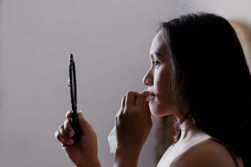 Mulher se olhando no espelho enquanto tira a maquiagem com um lenço.