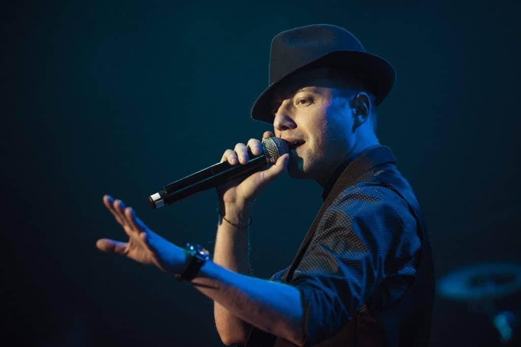 Imagem de um cantor negro segurando um microfone próxima a sua boca. Ele usa roupa e chapeu preto.