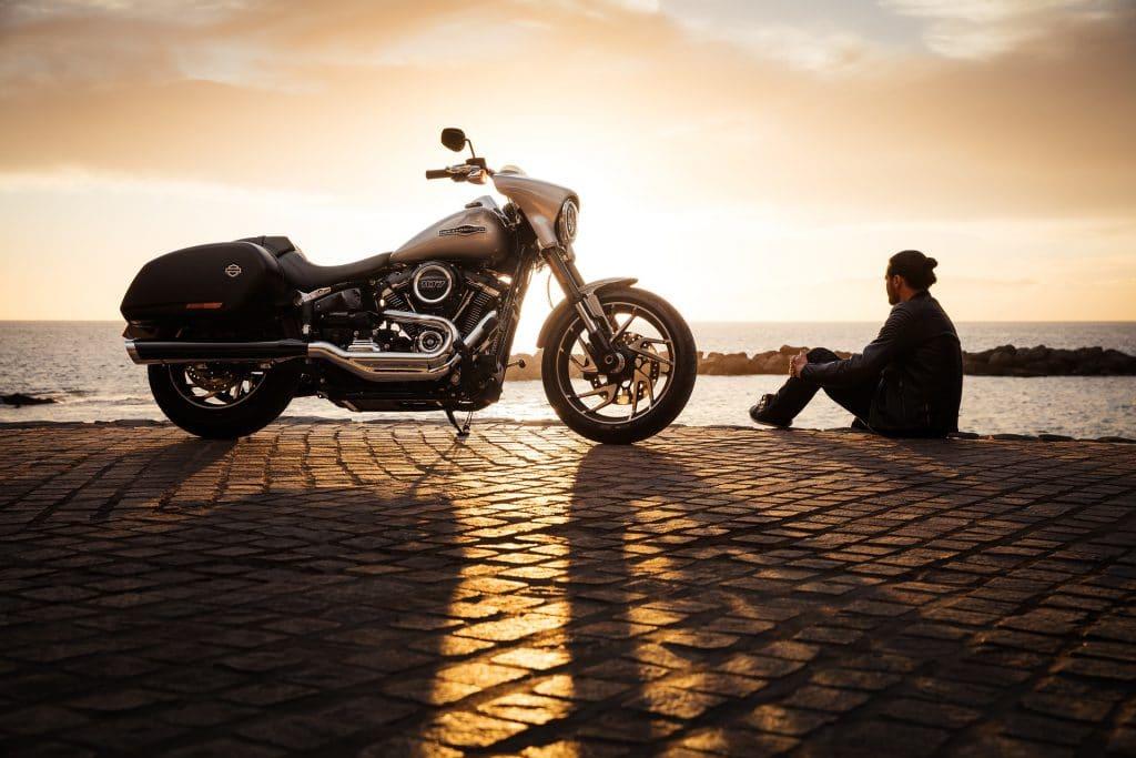 Imagem de um homem sentado em uma calçada de paralelepípedo. Ao lado dele uma linda moto. Ele está olhando para o infinito azul do mar.