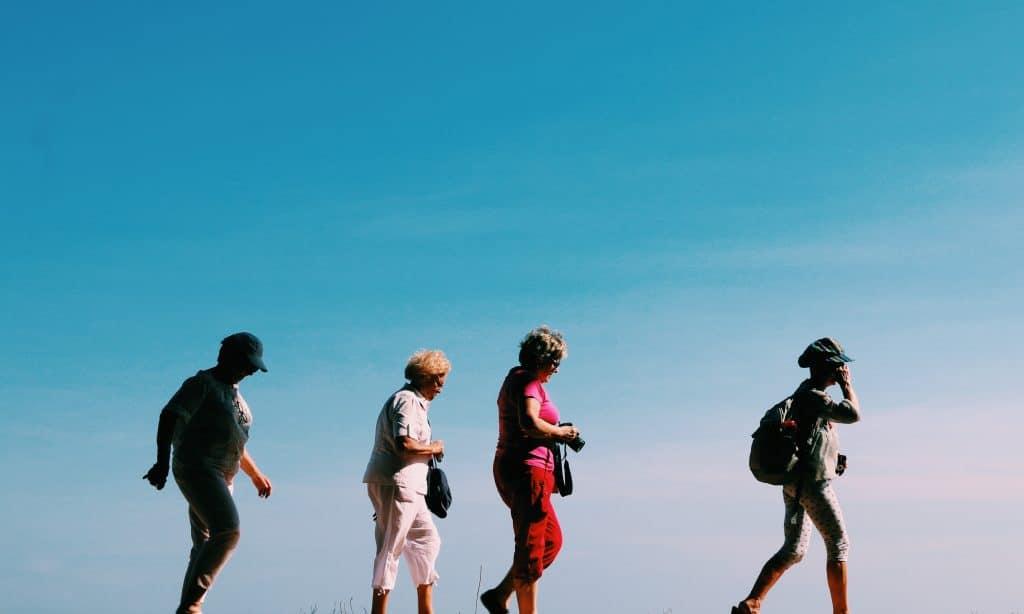 Quatro idosos caminhando enfileirados, durante o dia.