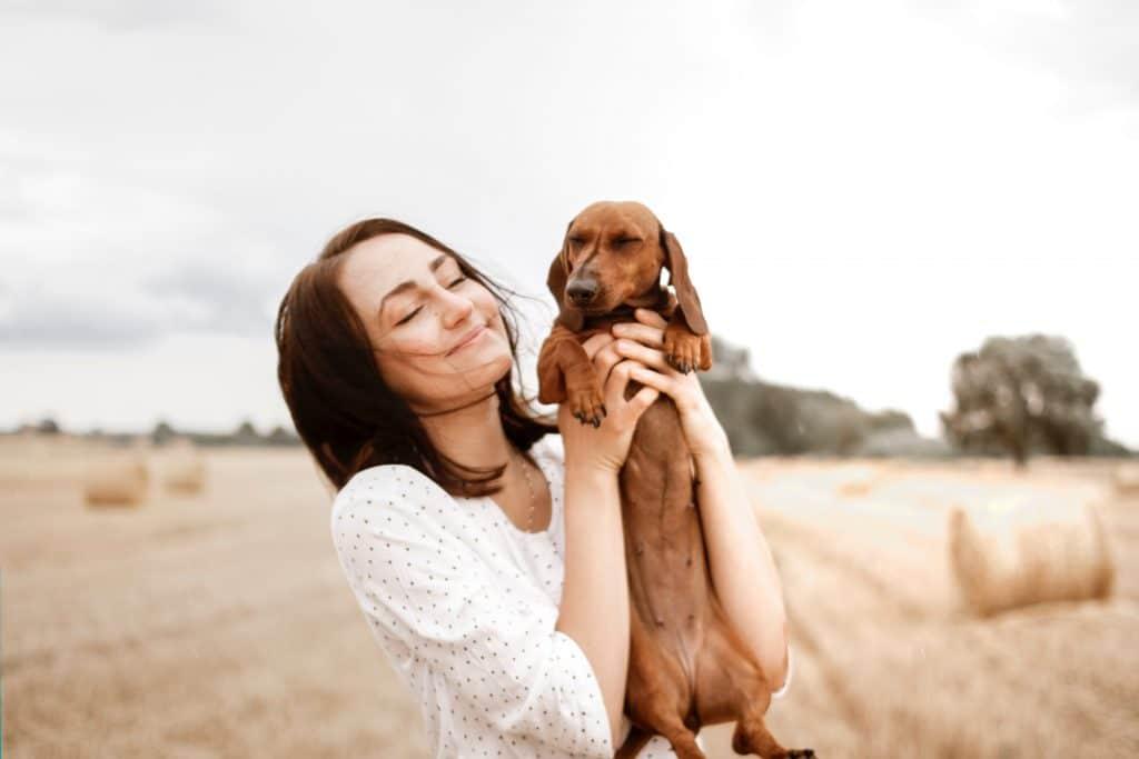 Mulher segurando cachorro no colo de olhos fechados em campo aberto