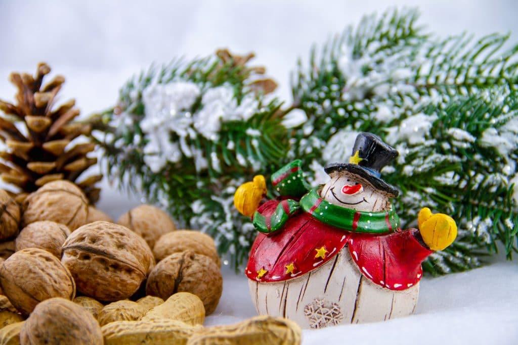 Imagem de nozes sobre uma mesa branca decorada com enfeites natalinos como pinha, boneco de neve e galho de um pinheiro.