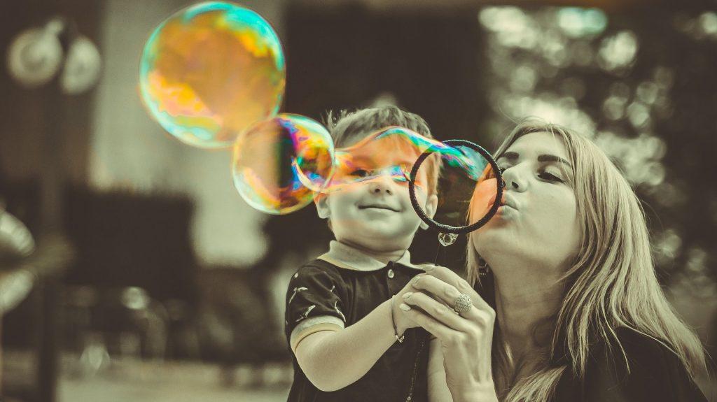 Mãe e filho em um parque. Ela segura as mãos da criança e um arco para fazer bolhas de sabão. A mãe está ensinando o filho a fazer as bolhas de sabão.