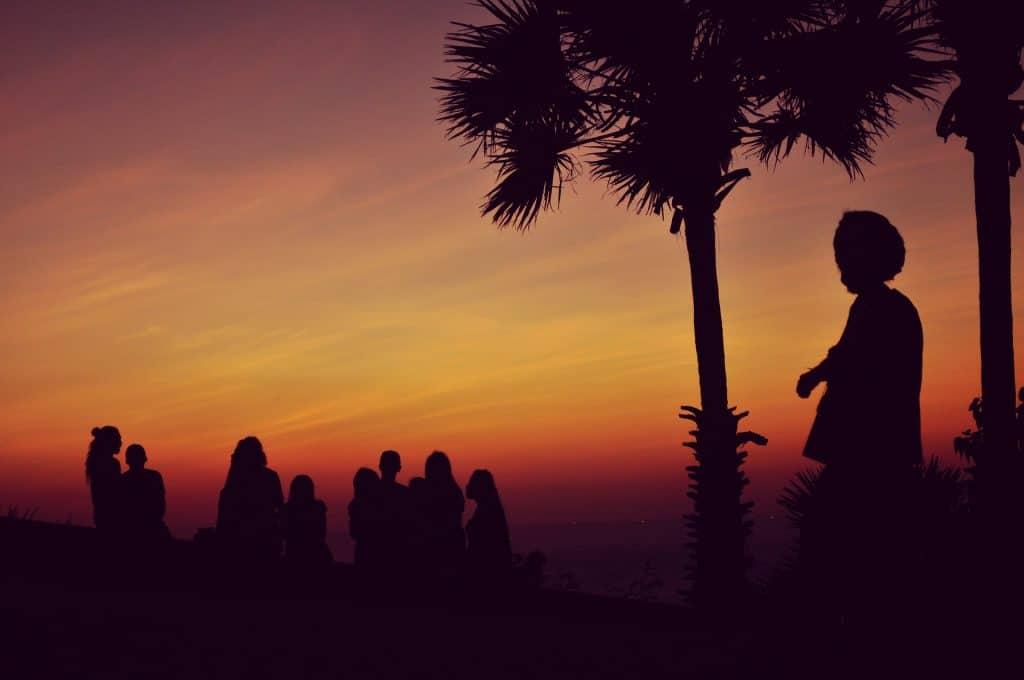 Imagem de um grupo de pessoas e um líder do estilo reggae em um campo alto assistindo o pôr do sol.