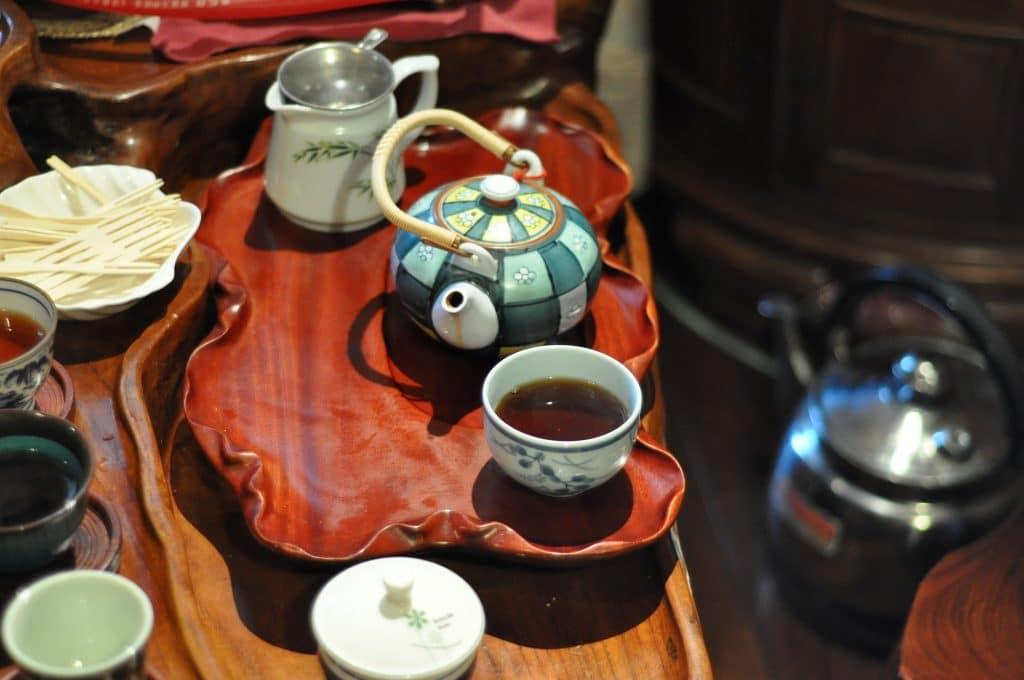 Imagem de uma cerimônia do chá. Sobre a mesa itens necessários para esse momento, como: bules de vários modelos, colheres específicas e bandejas em estilo madeira.