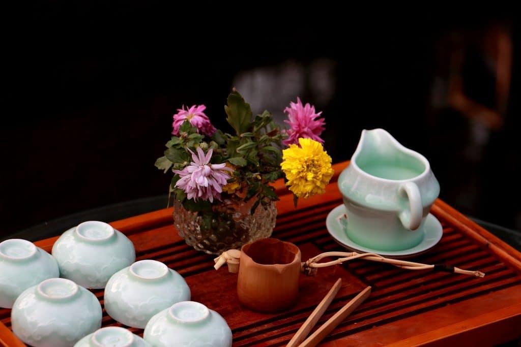 Imagem para a cerimônia do chá. Nela temos itens necessários para a realização desse evento: São balls, bule de porcelana dispostos sobre uma bandeja de madeira e um arranjo de flor colorido.