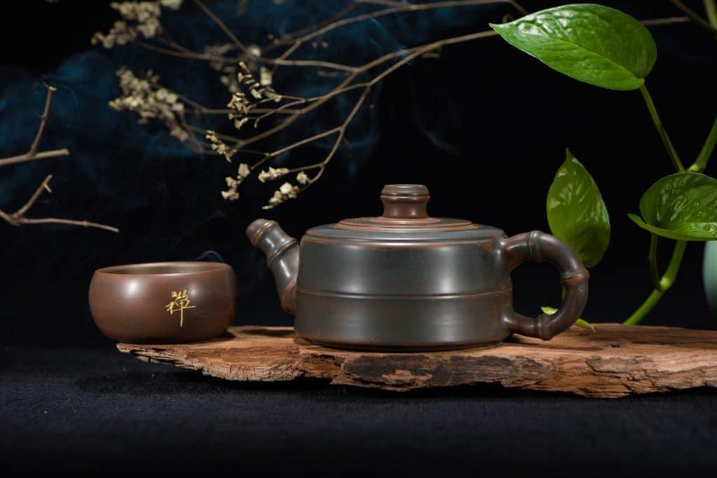 Imagem de um conjunto de chá composto por bule e uma cumbuca. Eles são feitos em material de bambu. Estão sobre uma madeira. Galhos de flores e uma folhagem verde decoram o ambiente.