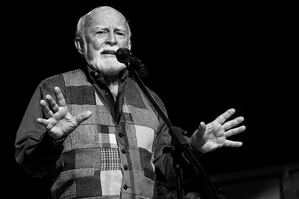 Homem idoso contando história em microfone, gesticulando com as mãos.