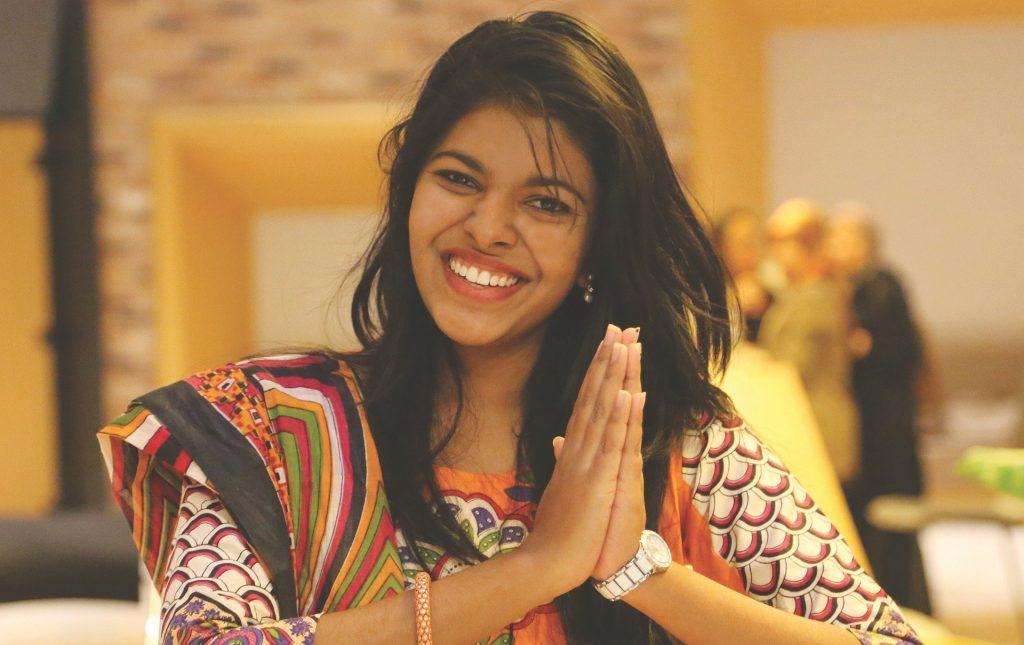Imagem de uma linda mulher de cabelos longos pretos. Ela sorri e faz o sinal de gratidão com as duas mãos.