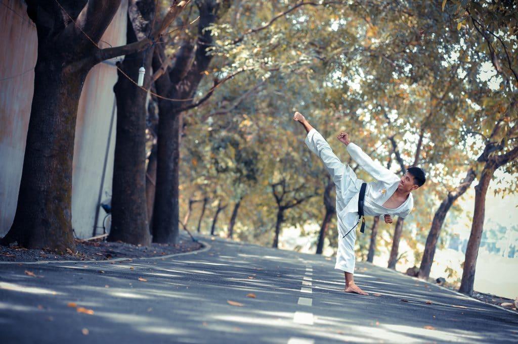 Homem praticando artes marciais no meio da rua