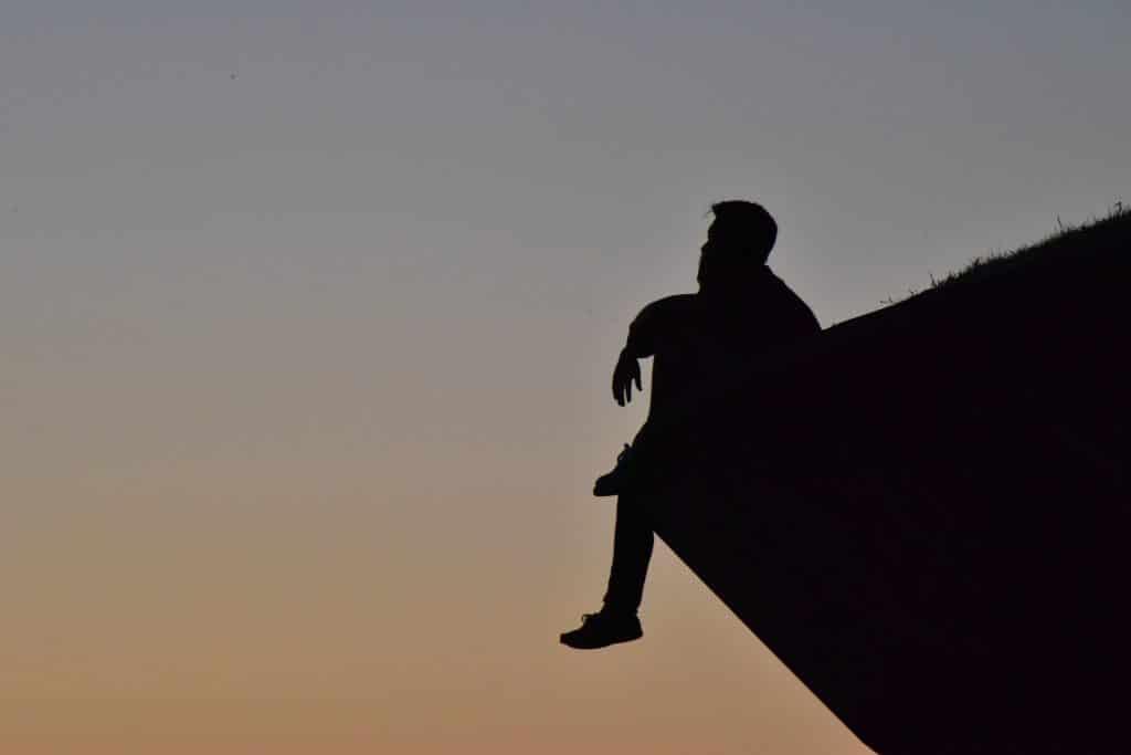 Silhueta de um homem pensando. Ele está sentado no pico de uma montanha.