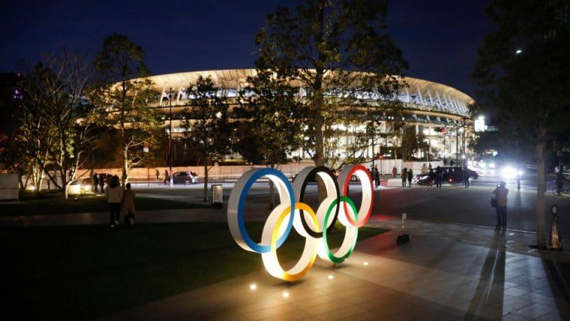 Uma estátua com os anéis olímpicos acesas durante a noite, e ao fundo um estádio iluminado em Tóquio.