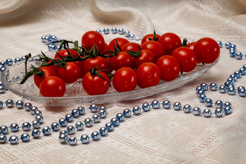 Travessa de vidro cheia de tomates cereja. A travessa está sobre uma mesa forrada com uma linda toalha de cetim bege decorada com um colar de bolas prateadas.