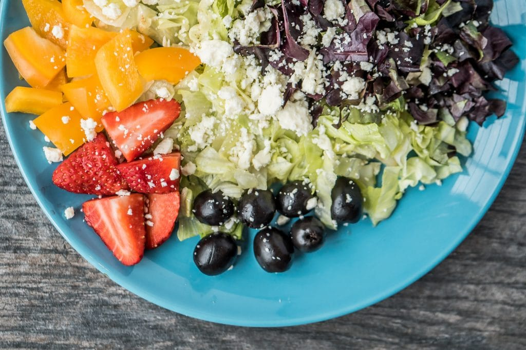 Prato de salada com folhas, azeitonas e frutas.