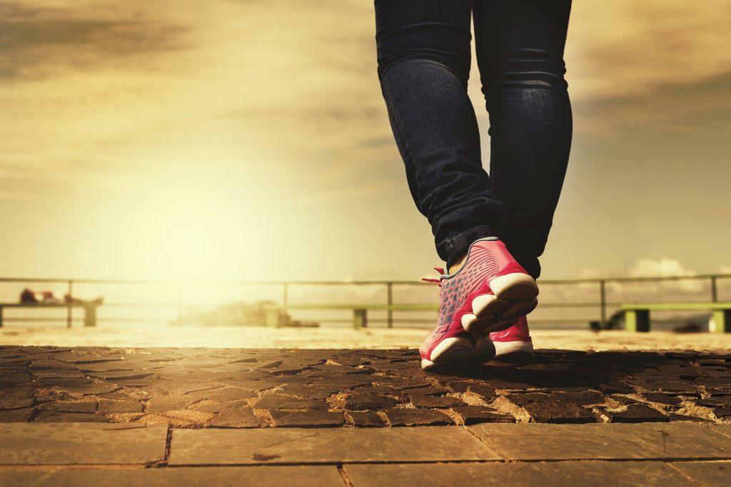 Imagem de uma perna feminina. A mulher usa tênis rosa e está caminhando na orla no início de um lindo dia ensolarado.